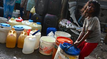 Seorang gadis menyeret ember berisi air yang dikumpulkan dari truk tangki air perusahaan kota di lingkungan berpenghasilan rendah di New Delhi pada Kamis (3/6/2021). Pada tahun 2018, lebih dari 600 juta orang di India tidak memiliki akses air bersih yang cukup. (Money SHARMA / AFP)