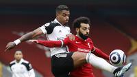 Pemain Fulham, Mario Lemina (kiri) mencuri bola dar penyerang Liverpool, Mohamed Salah, pada laga Liga Inggris di Stadion Anfield, Minggu (7/3/2021). (AFP/Phil Noble)