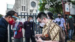 Seorang Jemaat memperlihatkan bukti pendaftaran untuk mengikuti ibadah di Gereja Katedral, Jakarta, Kamis (24/12/2020). 200 umat berada di dalam Gereja Katedral dan 109 umat berada di Plaza Maria. (Liputan6.com/Faizal Fanani)