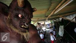 Sejumlah siswa menyaksikan Ogoh-ogoh yang akan di arak menjelang perayaan Nyepi di Pura Jagatnata,Yogyakarta, Senin (7/3/2016). Nyepi berasal dari kata sepi (sunyi, senyap). (Liputan6.com/Boy Harjanto)