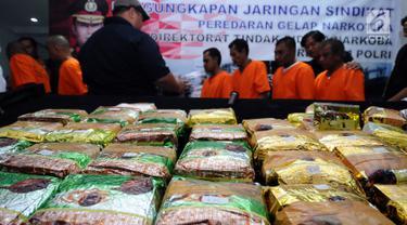Barang bukti narkotika berikut tersangka diperlihatkan petugas Dir IV Bareskrim Mabes Polri saat rilis di Jakarta, Senin (16/10). Dir IV Mabes Polri beserta Bea Cukai menggagalkan masuknya sabu seberat 30 kilogram. (Liputan6.com/Helmi Fithriansyah)