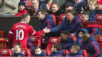 Penyerang Manchester United, Wayne Rooney, (kiri) bersalaman dengan pelatih Louis Van Gaal di bangku pemain pada laga melawan Aston Villa, Sabtu (16/4/2016). (EPA/Peter Powell)