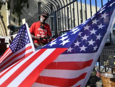 Bendera Amerika Serikat (AS) dikibarkan di tempat tinggal veteran yang bernama Kendrick Bailey di Los Angeles, California (10/11). Kendrick Bailey merupakan veteran AS yang pernah bertugas di Vietnam. (AFP Photo/Frederic J. Brown)