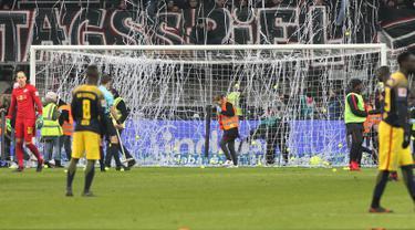 Suporter melempar bola tenis ke lapangan saat Kick-off  laga Eintracht Frankfurt melawan RB Leipzig di Stadion Commerzbank Arena, Senin (19/2). Mereka melakukan protes terhadap jadwal pertandingan Liga Jerman yang digelar Senin malam. (DANIEL ROLAND/AFP)