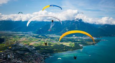 """Puluhan paraglider melakukan penerbangan menuju pendaratan """"Acro Show"""" di atas Danau Jenewa di Villeneuve, Swiss (20/8). Olahraga paragliding ini untuk tujuan rekreasi atau kompetisi. (Valentin Flauraud / Keystone via AP)"""