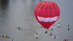 Para pedayung saat melihat balon udara yang terbang diatas danau Burley Griffin, Canberra,  Australia, (15/3). Ini dilakukan dilakukan dalam memperingati ulang tahun ke-30 festival Balloon Spectacular Canberra . (REUTERS / Lukas Coch)