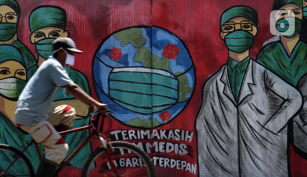 Pesepeda melintas di depan mural tentang pandemi virus COVID-19 di Jalan Raya Jakarta-Bogor, Depok, Selasa (7/4/2020). Mural tersebut ditujukan sebagai bentuk dukungan kepada tenaga medis yang menjadi garda terdepan menghadapi COVID-19 di Indonesia. (Liputan6.com/Helmi Fithriansyah)