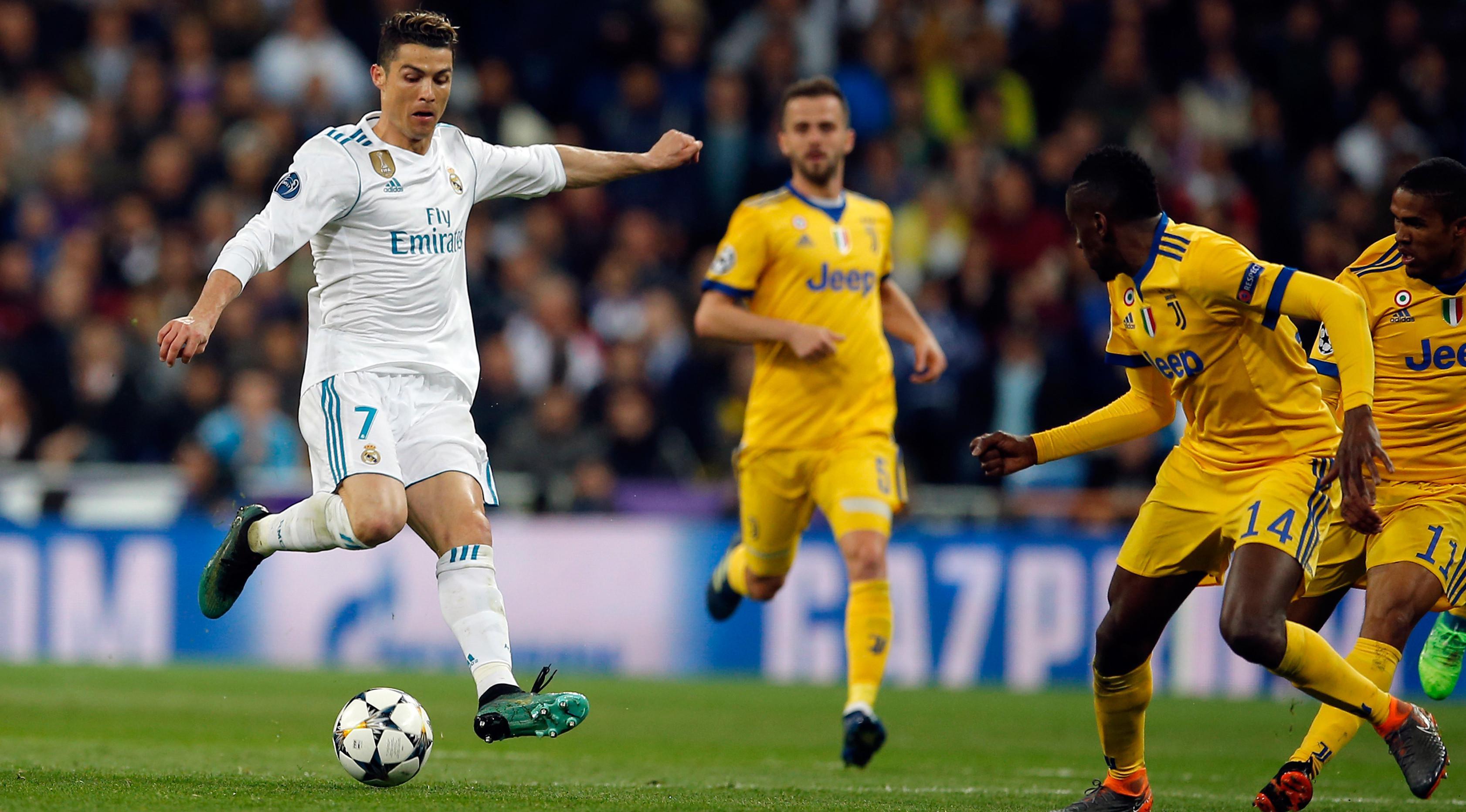 Pemain Real Madrid, Cristiano Ronaldo menendang bola dengan dibayangi pemain Juventus pada leg kedua babak perempat final Liga Champions di Santiago Bernabeu, Rabu (11/4) (AP/Paul White)