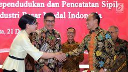 Dirjen Dukcapil Zudan Arif Fakrulloh (kanan) bersalaman dengan Dirut KSEI Friderica Widyasari Dewi usai penandatanganan kerja sama pemanfaatan data Ditjen Dukcail dengan 104 pelaku industri pasar modal, Jakarta, Jumat (21/12). (Liputan6.com/JohanTallo)