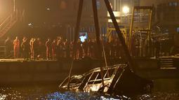 Sebuah crane mengevakuasi bus setelah jatuh dari jembatan ke Sungai Yangtze di Chongqing barat daya China (1/11). Bus berisikan 15 orang jatuh ke Sungai Yangtze, China pada Minggu (28/10). (AFP Photo/Str)