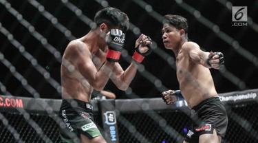 Dua petarung Indonesia, Rizki Umar (kiri) menahan pukulan petarung Arnol Batubara (kanan) saat berlaga pada seri pertama dalam One Championship di Jakarta, Sabtu (20/1). Riski Umar langsung mengajak Arnol bermain keras. (Liputan6.com/Faizal Fanani)