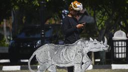 Pelajar bermain ponselnya sambil membawa gambar badak saat melakukan aksi di peringatan Hari Bumi di Aceh (22/4). Peringatan hari bumi ini bertepatan dengan aksi Global March untuk Gajah, Harimau, Badak dan Orang Utan yang juga dilakukan serentak di banyak negara. (AFP Photo/Chaideer Mahyuddin)
