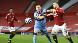 Bek Manchester United, Luke Shaw, berebut bola dengan pemain West Ham United, Vladimir Coufal, pada laga Liga Inggris di Stadion Old Trafford, Minggu (15/3/2021). Setan Merah menang dengan skor 1-0. (AP/Clive Brunskill,Pool)