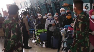Petugas mengarahkan rombongan jemaah umrah yang tiba di Bandara Soekarno Hatta, Tangerang, Selasa (29/12/2020). Rombongan jemaah umrah yang baru tiba di Indonesia tersebut diarahkan untuk melakukan karantina di tempat yang telah disediakan oleh pemerintah. (Liputan6.com/Angga Yuniar)
