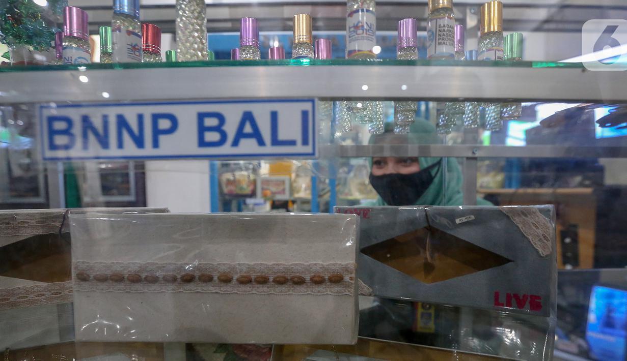Penjaga toko menata kerajinan tangan di gerai Toko Stop Narkoba, Gedung BNN, Cawang, Jakarta, Jumat (24/7/2020). Toko Stop Narkoba tersebut memasarkan hasil kerajinan tangan karya warga binaan BNN dari berbagai provinsi yang dapat dibeli secara langsung maupun via daring. (Liputan6.com/Fery Pradolo)