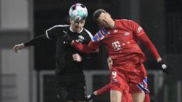 Striker Bayern Munich, Robert Lewandowski (kanan) berduel udara dengan bek tim Divisi 2 Holstein Kiel, Marco Komenda dalam laga babak kedua Piala DFB Pokal 2020/21 di Kiel, Rabu (13/1/2021). Bayern Munich kalah dari Holstein Kiel lewat adu penalti 5-6 (2-2). (AFP/Fabian Bimmer/Pool)