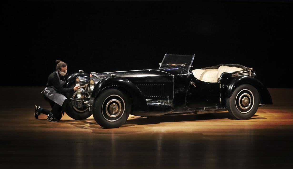 Sebuah Bugatti Type 57S 1937, salah satu mobil pra-perang paling berharga, dipoles oleh staf di rumah lelang Bonhams di London, Selasa (16/2/2021). Seri yang termasuk diburu kolektor mobil langka ini diperkirakan akan terjual 6,95 juta sampai 9,73 juta dollar AS. (AP Photo/Frank Augstein)