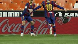 Penyerang Barcelona, Antoine Griezmann berselebrasi dengan rekannya Lionel Messi usai mencetak gol ke gawang Valencia pada pertandingan La Liga Spanyol di stadion Mestalla, Senin (3/5/2021). Barcelona menang tipis atas Valencia 3-2. (AP Photo/Alberto Saiz)