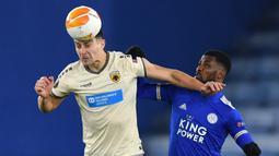 Bek AEK Athens, Ionut Nedelcearu (kiri), berduel udara dengan striker Leicester City, Kelechi Iheanacho, dalam laga lanjutan Liga Europa 2020/21 Grup G di King Power Stadium, Kamis (10/12/2020). AEK Athens kalah 0-2 dari Leicester City. (AFP/Ben Stansall)