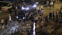 Sebuah van polisi membubarkan suporter Manchester City yang rusuh di tepi sungai Douro di Porto, Portugal (28/5/2021).  Sejumlah suporter Manchester City bentrok dengan polisi di Porto, Portugal, jelang final Liga Champions. (AP Photo/Luis Vieira)