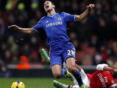 Bek Chelsea Cesar Azpilicueta mendapatkan tekel keras dari striker Arsenal Theo Walcott pada pertandingan sepak bola Liga Inggris antara Arsenal vs Chelsea di Stadion Emirates, London (24/12/13). (AFP/Adrian Dennis)