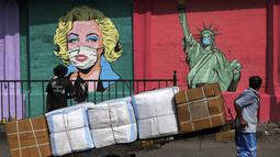Pekerja membawa barang-barang di gerobak sambil melihat seniman melukis mural pencegahan virus corona di Mumbai (26/3/2021). India juga tengah mengalami lonjakan mengkhawatirkan yang membuat negara tersebut akan kembali melakukan pembatasan pada pertemuan publik. (AP Photo/Rajanish Kakade)