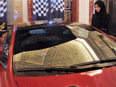 Dua wanita Saudi melihat sebuah mobil di sebuah pameran mobil di resor Jeddah Laut Merah Jeddah (5/10). Pada bulan September 2017 Kerajaan Arab Saudi mengeluarkan dekrit yang memperbolehkan wanita untuk mengendarai mobil. (AFP Photo/Amer Hilabi)