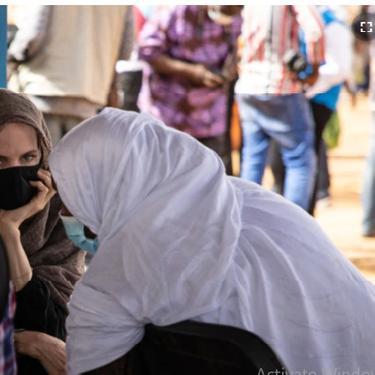 Aktris Angelina Jolie, utusan khusus badan PBB untuk urusan pengungsi (UNHCR), berbincang-bincang dengan Pengungsi Mali di Kamp Goudebo, di utara Burkina Faso, dalam peringatan Hari Pengungsi Sedunia, Minggu, 20 Juni 2021. (Olympia de Maismont/AFP)