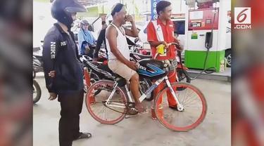 Pria ini mengisi sepeda modifikasinya gunakan bensin. Aksinya pun berbuah perhatian masyarakat sekitar.