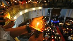 Umat Kristiani menyalakan lilin pada misa malam Natal di Gereja Immanuel, Jakarta  Sabtu (24/12). Perayaan natal berlangsung khidmat. (Liputan6.com/Angga Yuniar)