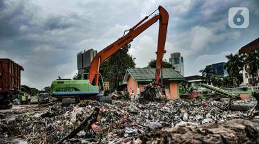 Petugas UPK Badan Air DLH Provinsi DKI Jakarta mengangkut sampah sungai memakai alat berat di TPSS Perintis Kemerdekaan, Jakarta, Selasa (16/2/2021). Selama musim hujan, volume sampah yang diangkut dari sungai di Jakarta meningkat hingga 600 meter kubik per hari. (merdeka.com/Iqbal S. Nugroho)