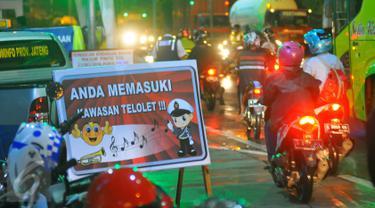 Sebuah plang bertuliskan kawasan telolet dipasang di jalur pantura Brebes, Jawa Tengah, Jumat (23/12). Demam Telolet yang saat ini sedang membuming membuat petugas kepolisian setempat memasang Papan tersebut. (Liputan6.com/Angga Yuniar)