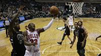 Penggawa Chicago Bulls Kris Dunn coba memasukkan bola pada laga NBA 2017-2018 melawan Milwaukee Bucks di BMO Harris Bradley Center, Jumat (15/12/2017) atau Sabtu (16/12/2017) WIB. (AP Photo/Morry Gash)
