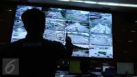 Petugas memantau CCTV di ruangan NTMC Polda Metro Jaya, Jakarta, Selasa (25/10). Korps Lalu Lintas Polri tengah merancang pembayaran tilang kendaraan menggunakan sistem online. (Liputan6.com/Gempur M Surya)