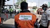 Seorang warga mengenakan rompi pelanggar PSBB akibat tidak mengenakan masker di area Pasar Kramat Jati, Jakarta, Rabu (17/6/2020). (merdeka.com/Iqbal S. Nugroho)