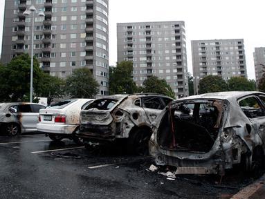 Deretan mobil yang terparkir di kota Gothenburg, Swedia hangus dan rusak, Selasa (14/8). Sekelompok orang bertopeng dan berpakaian hitam dilaporkan menjadi pelaku pembakaran puluhan mobil di sejumlah kota dalam semalam. (Adam Ihse/TT via AP)