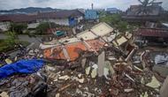 Pengemudi melewati bangunan yang diratakan oleh gempa bumi di Mamuju, Sulawesi Barat, Sabtu (16/1/2021). Petugas Badan Penanggulangan Bencana Daerah (BPBD) masih mendata jumlah kerusakan dan korban akibat gempa bumi tersebut. (AP Photo/Yusuf Wahil)