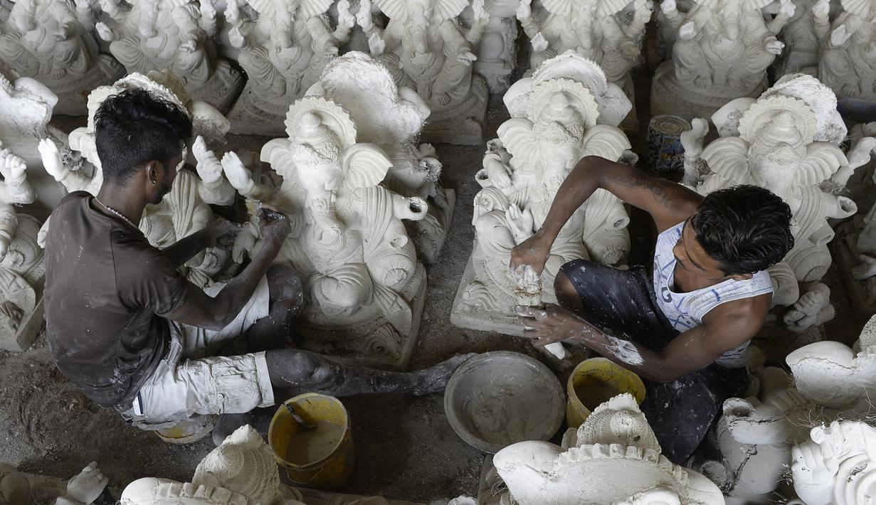 Para perajin menyelesaikan pembuatan patung Dewa Ganesha di sebuah bengkel di pinggiran Hyderabad, India, Senin (29/6/2020). Patung Dewa Ganesha banyak ditemukan di berbagai penjuru India termasuk Nepal, Tibet, dan Asia Tenggara. (NOAH SEELAM/AFP)
