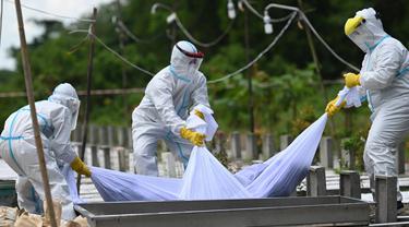 Relawan yang mengenakan pakaian pelindung diri (APD) menurunkan ke dalam kuburan jenazah seseorang yang diduga meninggal akibat virus Corona Covid-19 di sebuah pemakaman, di Yangon (26/10/2020). (AFP/Ye Aung Thu)