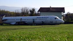 Dua wanita membersihkan badan pesawat Fokker-100 di halaman rumah warga setempat di Strmec Stubicki, Kroasia, 26 Oktober 2019. Pesawat yang membujur di kebun Robert Sedlar (50) itu merupakan buatan 1991 dan beroperasi melayani penerbangan komersial di Kroasia sampai 2014. (Denis LOVROVIC / AFP)