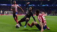 Gelandang Liverpool, Mohamed Salah, berebut bola dengan bek Atletico Madrid pada leg pertama 16 besar Liga Champions di Stadion Wanda Metropolitano, Madrid, Rabu (19/2) dini hari WIB. Atletico menang 1-0 atas Liverpool. (AFP/Oscar Del Pozo)