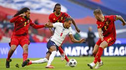 Striker Inggris, Dominic Calvert-Lewin, berusaha melewati pemain Belgia pada laga UEFA Nations League di Stadion Wembley, Minggu (11/10/2020). Inggris menang dengan skor 2-1. (Michael Regan/Pool via AP)