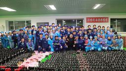 Pemimpin Korea Utara, Kim Jong-Un foto bersama sejumlah pekerja saat mengunjungi pabrik sepatu Wonsan, Korea Utara (3/12). (Photo by KCNA VIA KNS / various sources / AFP)