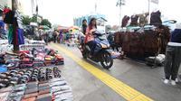 Pengendara motor melintas diatas trotoar yang samping kanan-kirinya dipenuhi pedagang kaki lima di Jalan Kebon Jati, Tanah abang, Sabtu (23/12). (Liputan6.com/Angga Yuniar)