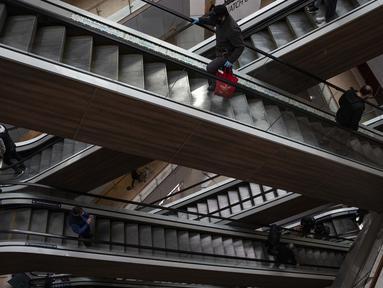 Orang-orang menaiki eskalator yang kosong saat pembukaan kembali pusat perbelanjaan Costanera di Santiago, Chile, 18 Agustus 2020. Pihak berwenang Chile berharap melanjutkan peta jalan untuk membuka kembali Ibu Kota secara penuh, sambil menerapkan jarak sosial yang ketat. (AP Photo/Esteban Felix)