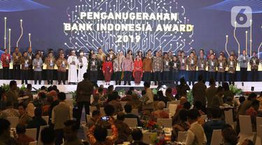 Gubernur Bank Indonesia Perry Warjiyo (tengah) berfoto bersama para penerima penghargaan BI 2019 saat acara yang sekaligus penyerahan penghargaan Bank Indonesia (BI) dalam Pertemuan Tahunan Bank Indonesia (PTBI) 2019 di Jakarta, Kamis (28/11/2019). (Liputan6.com/Angga Yuniar)