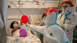 Para badut medis menghibur seorang pasien COVID-19 di ruang perawatan Ziv Medical Center di Kota Safed, Israel utara, pada 19 November 2020. (Xinhua/JINI/Erez Ben Simon)