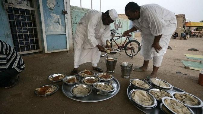 Beberapa warga Sudan terlihat sedang menyiapkan makanan sebelum makan malam Iftar di pinggir jalan raya Khartoum di desa al-Nuba (AFP)
