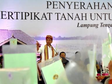 Presiden Joko Widodo saat menyerahkan langsung 1.300 sertifikat hak atas tanah untuk masyarakat di Kabupaten Lampung Tengah, Jumat (23/11). Penyerahan sertifikat ini dilakukan di Gedung Lapangan Tenis Pemda Lampung Tengah. (Liputan6.com/HO/Biropers)
