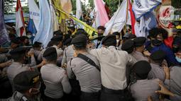 Polisi saling dorong dengan mahasiswa yang tergabung dalam Aliansi BEM Seluruh Indonesia (BEM SI) saat menggelar aksi di sekitar Gedung Merah Putih KPK, Jakarta, Senin (27/9/2021). Polisi menahan mahasiswa untuk merangsek maju. (Liputan6.com/Faizal Fanani)